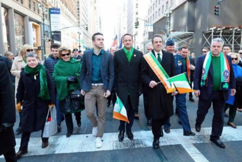 Leo Varadkar and Michael Barrett walking in front of a parade of people with people holding irish flags