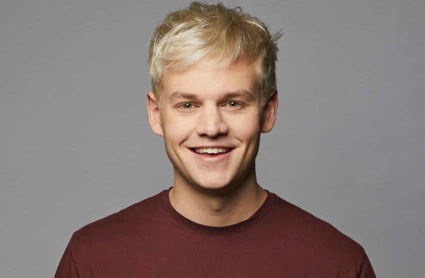 Head shot of Joel Creasey, he's wearing a maroon t-shirt and smiling
