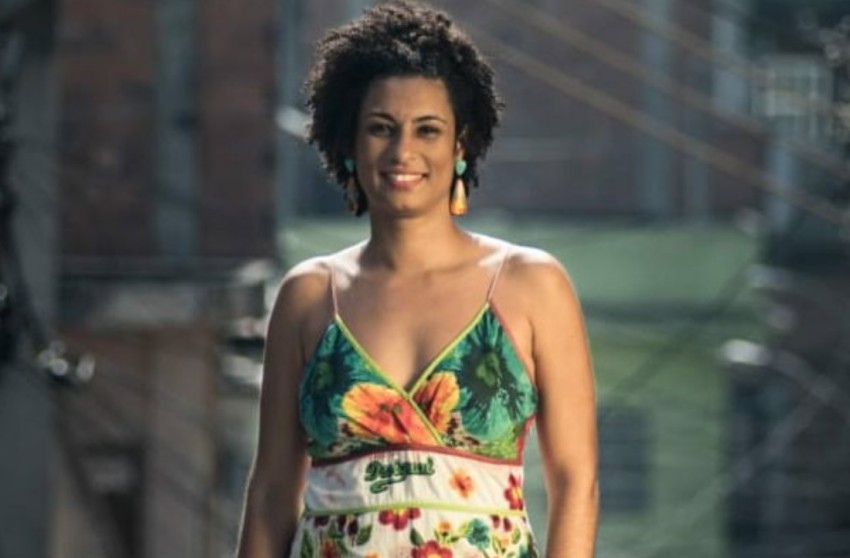 Marielle Franco stands smiling at camera on the street of a rio favela