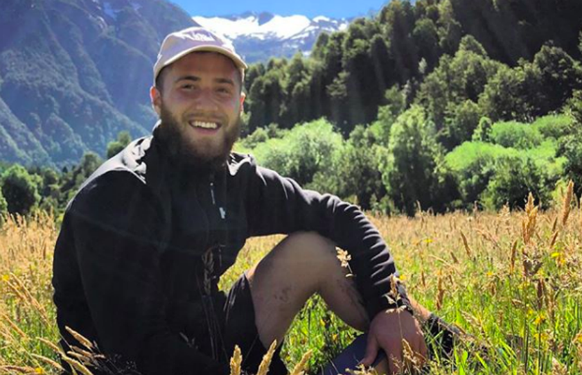 Mike Posner sat in a field on a hill, in Chilean Patagonia