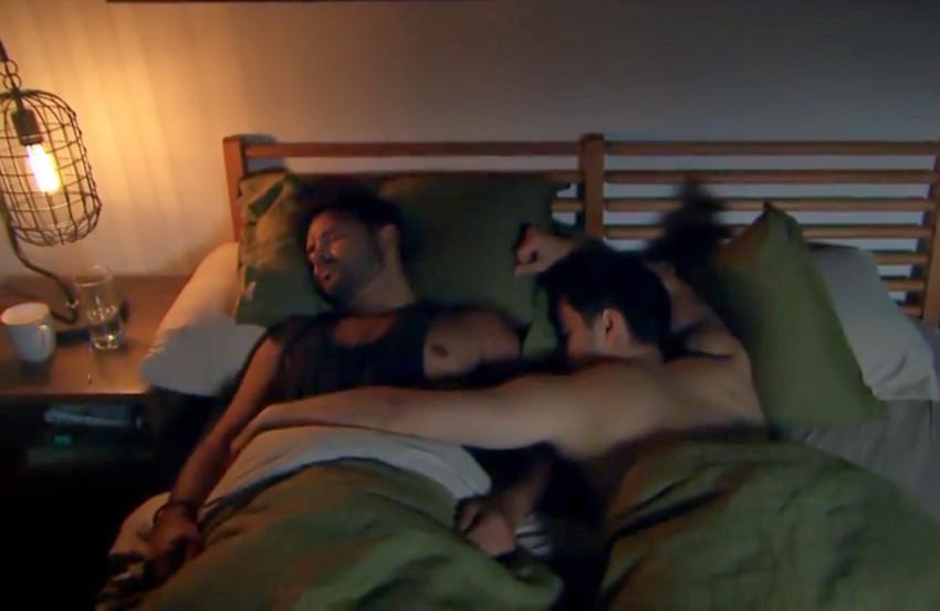 Two men lying in bed sleeping next to each other, one man has his arm across the other man's stomach