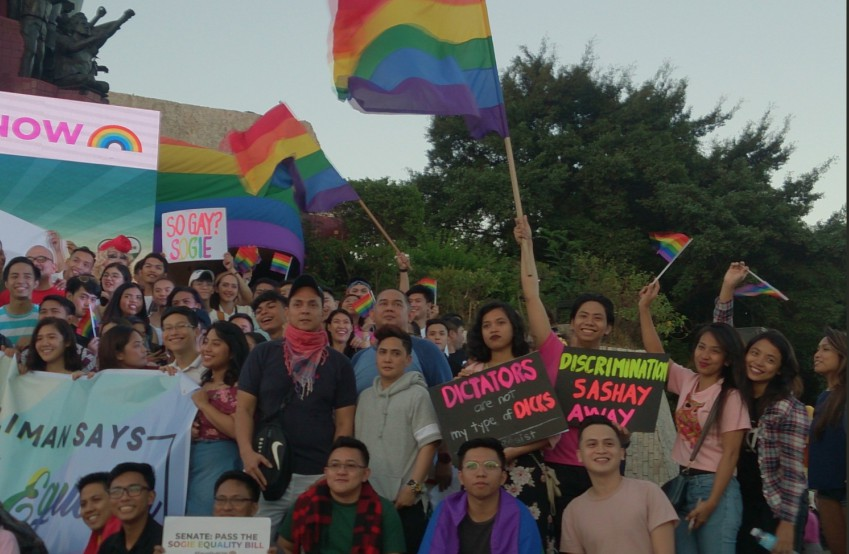 Hundreds of people stand at the base of the people power monument holding rainbow flags and colourful placards