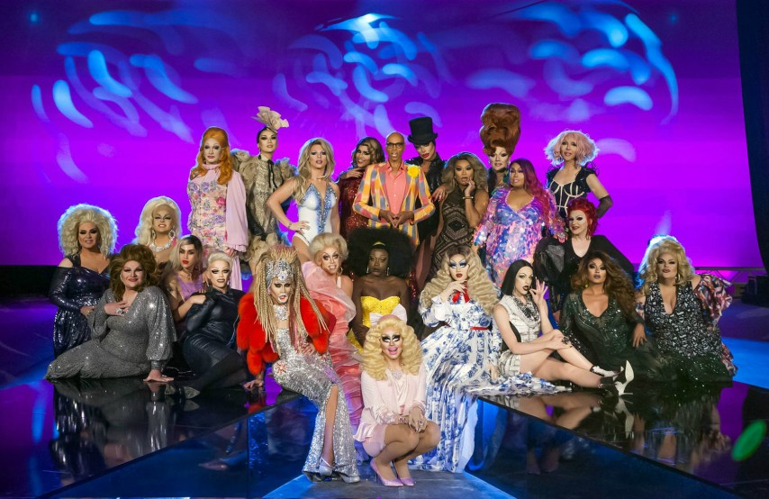 A group of drag queens on a stage surrounding RuPaul
