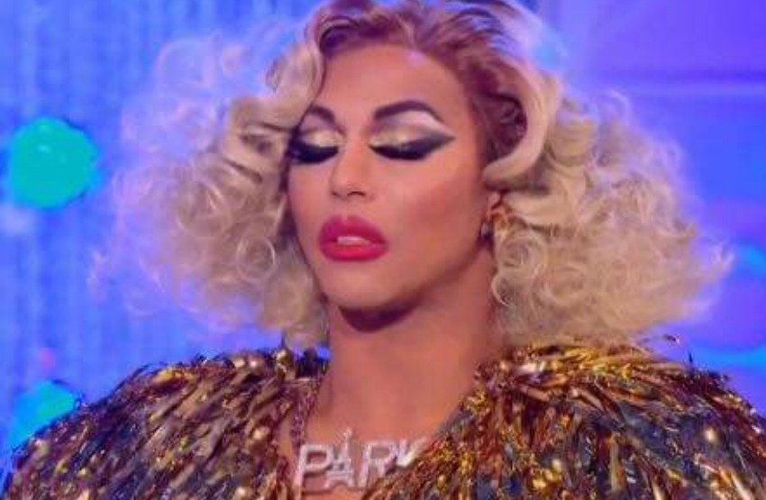 Close up of Shangela's face, she is wearing a gold jacket with logo necklace spelling paris. She has a blonde wing on and her eyes are closed.