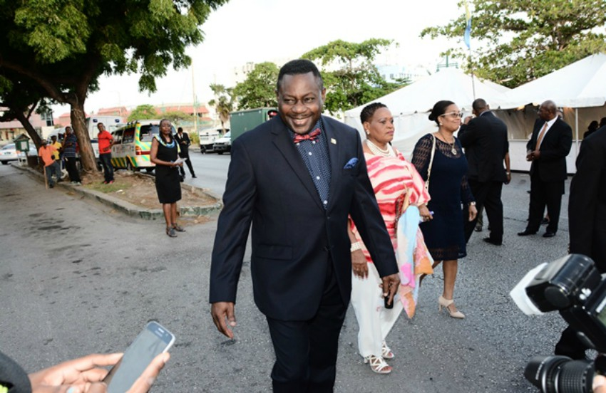 Steven Blackett in suit with red bowtie walks past a crowd of reporters outside
