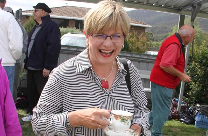 Allison Standen stands at a public event holding a cup and saucer and laughing at the camera