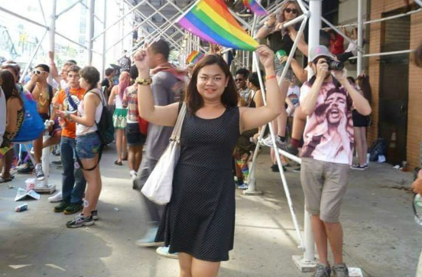 Kath Khangpiboon stands on a busy street wearing a black dress holding a rainbow flag over her head