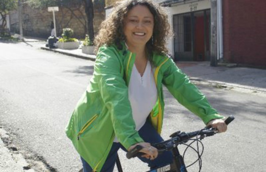 Angélica Lozano on a bicycle in the street she's wering a green jacket
