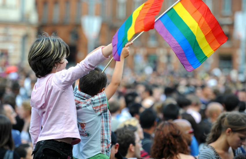 Two kids wave rainbow flag at Pride event