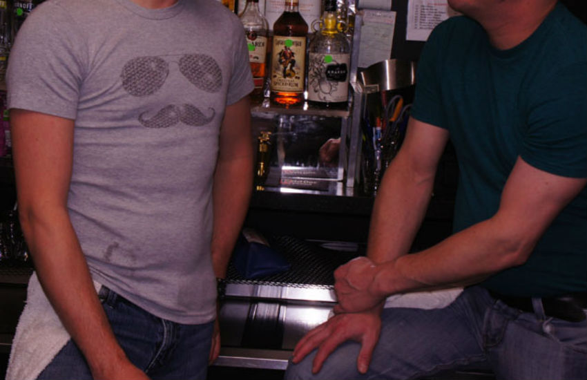 Two guys behind a bar with one being hit on
