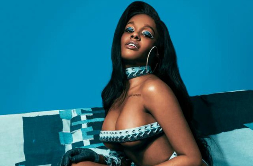 Azealia Banks sits on a couch with a blue background and is sitting side on to the camera in a skimpy leather outfit