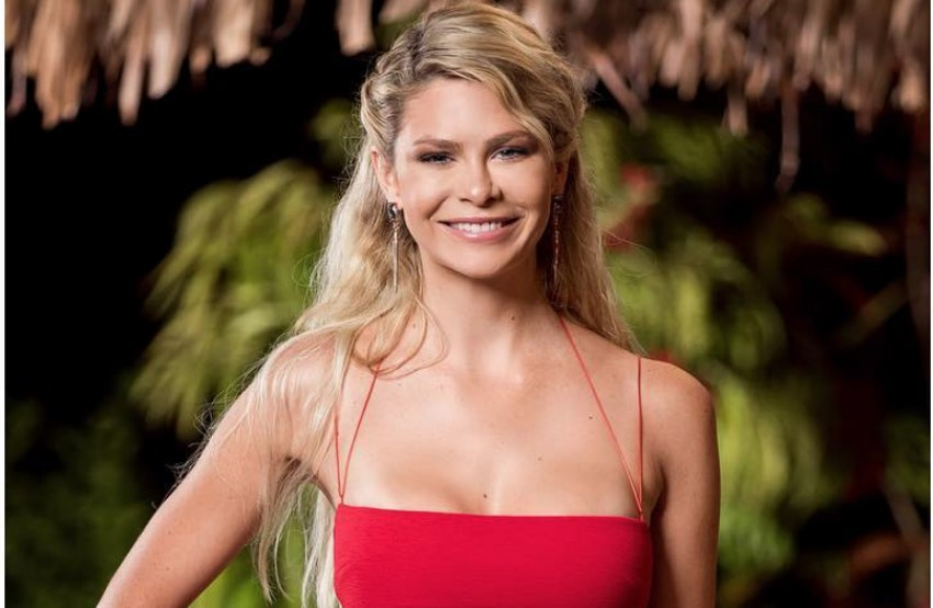 A head and shoulder shot of megan marx standing in a tropical location. Her long blonde hair is half-up, half-down and she is wearing a red crop top with spaghetti straps