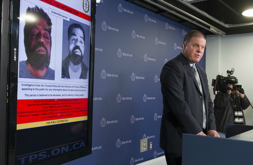 Hank Idsinga stands at a podium addressing media, behind him is a photo of of a deceased man