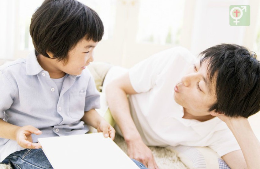 A father and son talking to each other. The father is lying on his side with his head resting on his hands looking at his son. The son about 6 years old is sitting up with paper in his lap and is smiling at his dad