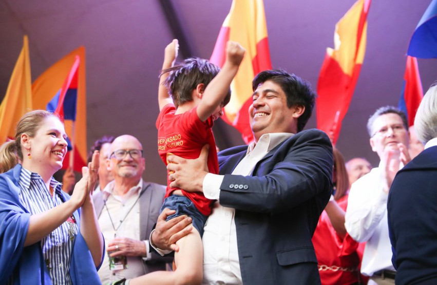 Carlos Alvarado on stage smiling holding a child throwing his arms in the area surround by flags and people cheering