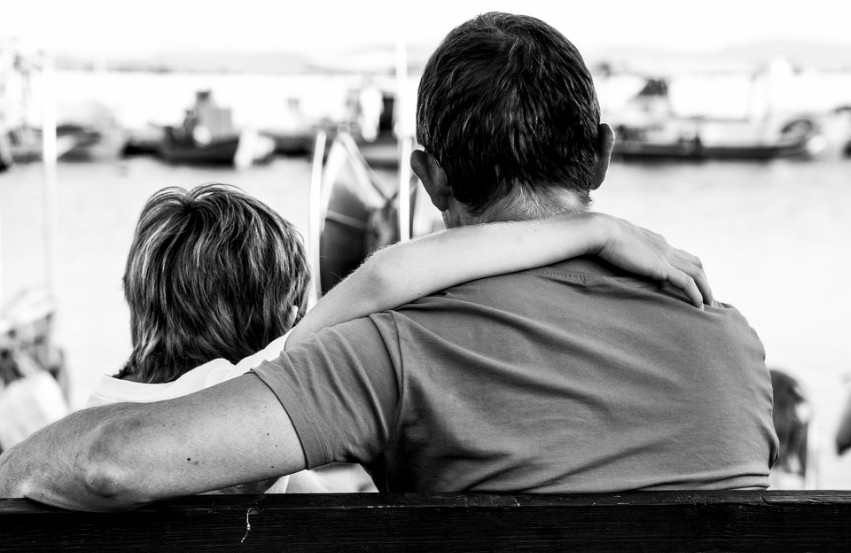 black and white photo, of a man and young boy with their arms around each other, their backs are to the camera and they're facing water