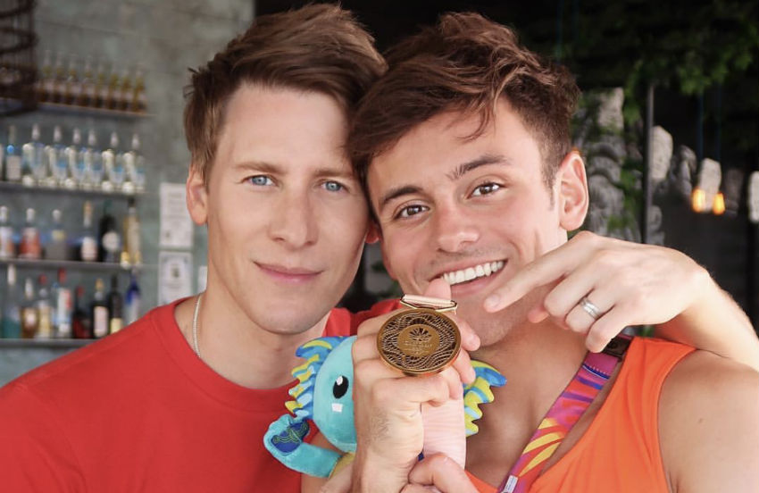 Dustin Lance Black and Tom Daley hold up the gold medal Daley won at the Commonwealth Games in Australia earlier this month