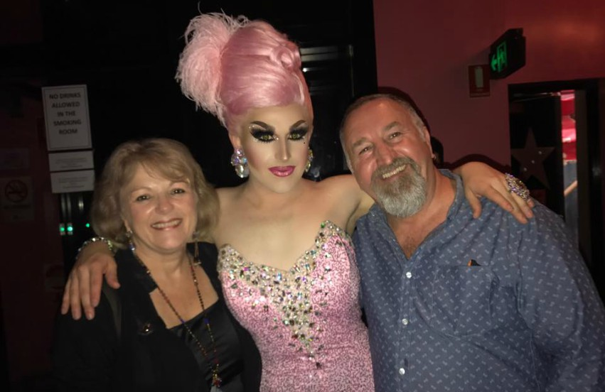three people standing in night club, the middle person is a drag queen wearing a pink dress and feather headpiece, she has her arms draped around the other two