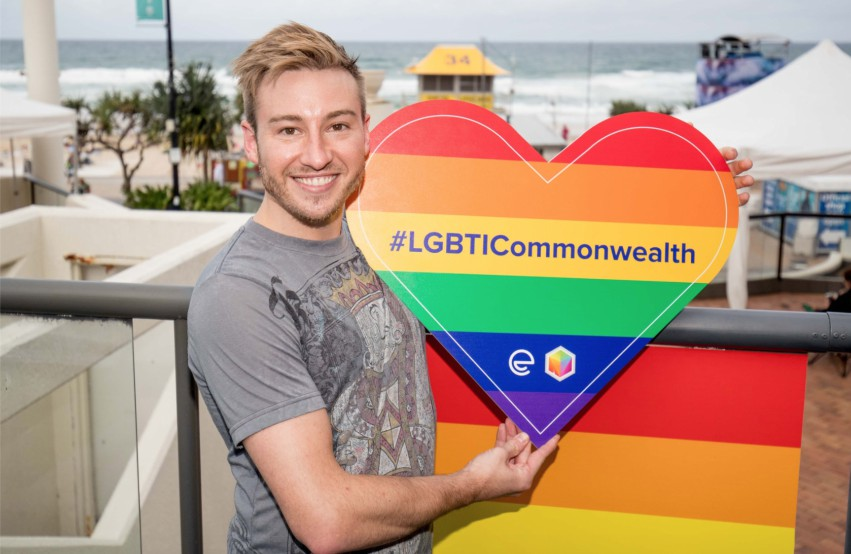 Matthew Mitcham stands in front of railing near the beach holding a big love heart with rainbow colours that says #Lgbticommonwealth