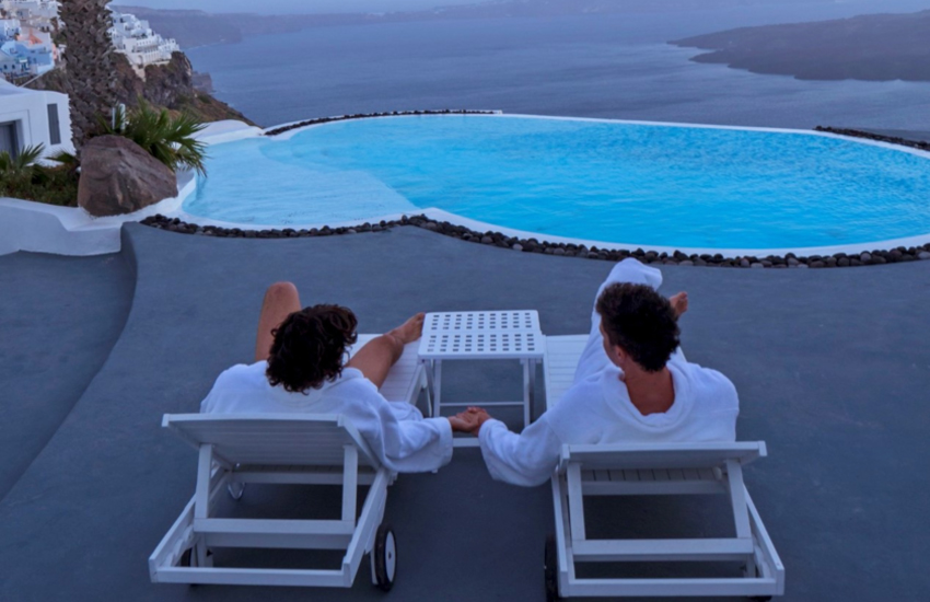 A couple by a pool in Santorini