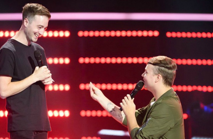 Two men facing each other one is on his knees holding a ring up and speaking into a microphone the other is standing looking down at him. they are on a stage with bright red lights