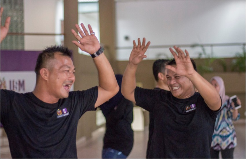Two men in black t-shirts facing each other with their arms in the air and smiling at each other