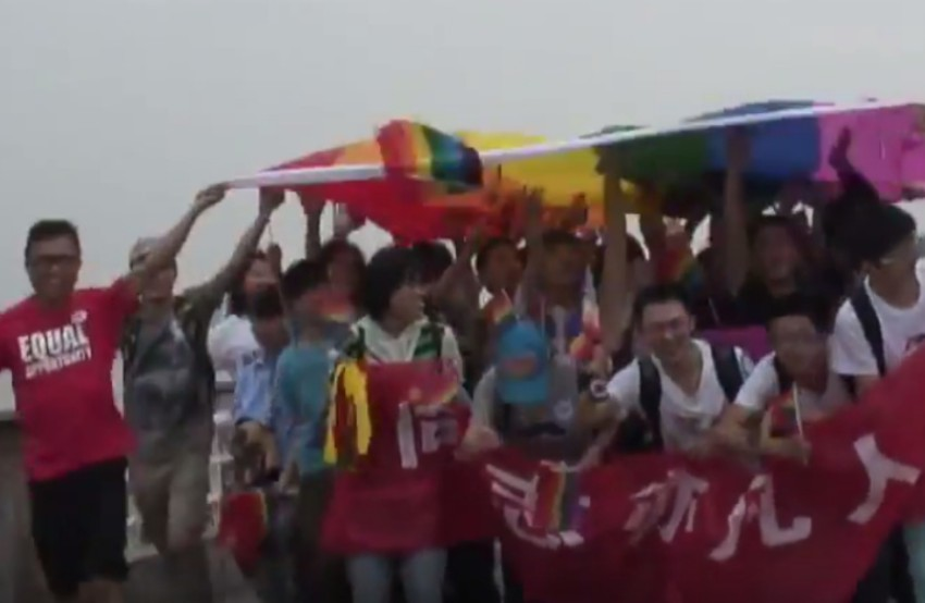A group of people holding banners looking happy and standing under a giant rainbow flag