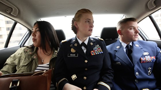 Three people in the back of a car looking at the windows, two are wearing military uniforms