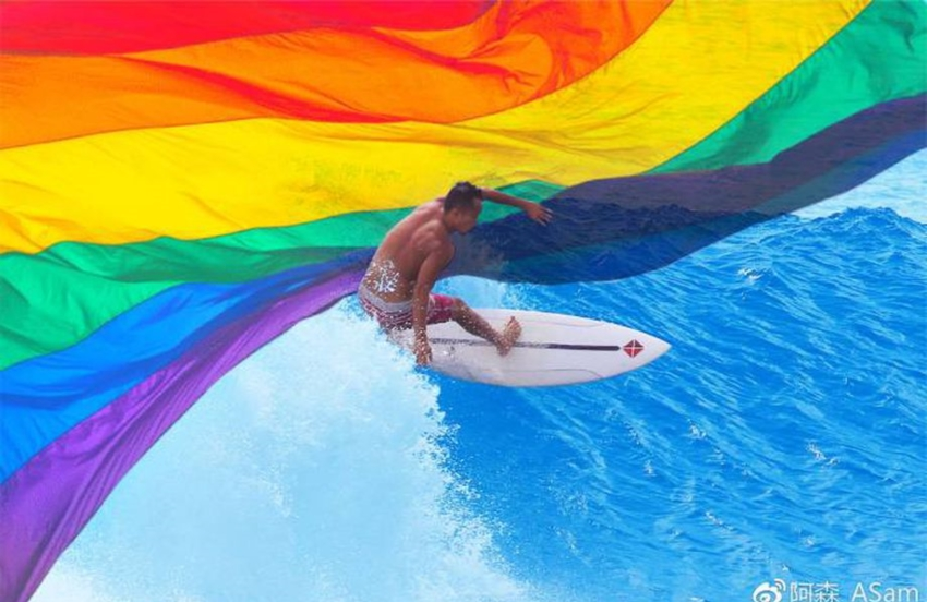 a man on a surfboard riding a wave with a rainbow flag superimposed in the top third of the photo