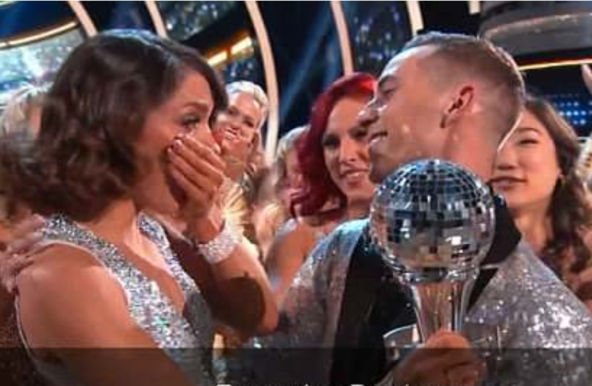 A close up of jenna and adam after winning jenna has her hand over her mouth looking at adam who is smiling and holding the mirror ball trophy he is smiling. they are surrounded by people