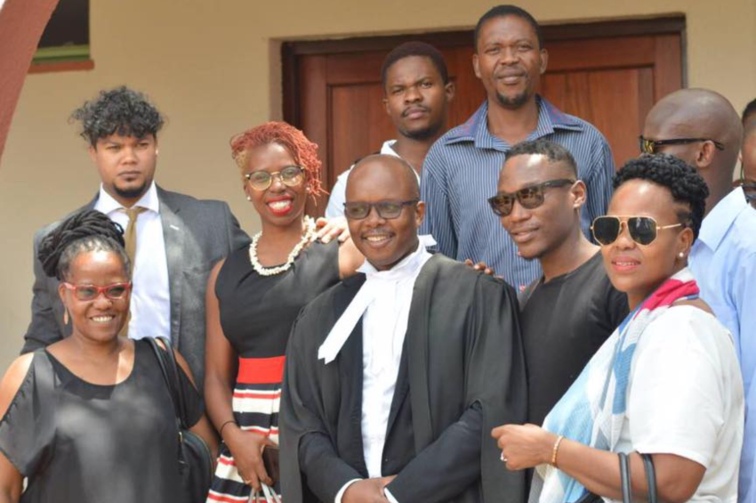 a group of people standing on a step surrounding a lawyer in robes and they are all smiling