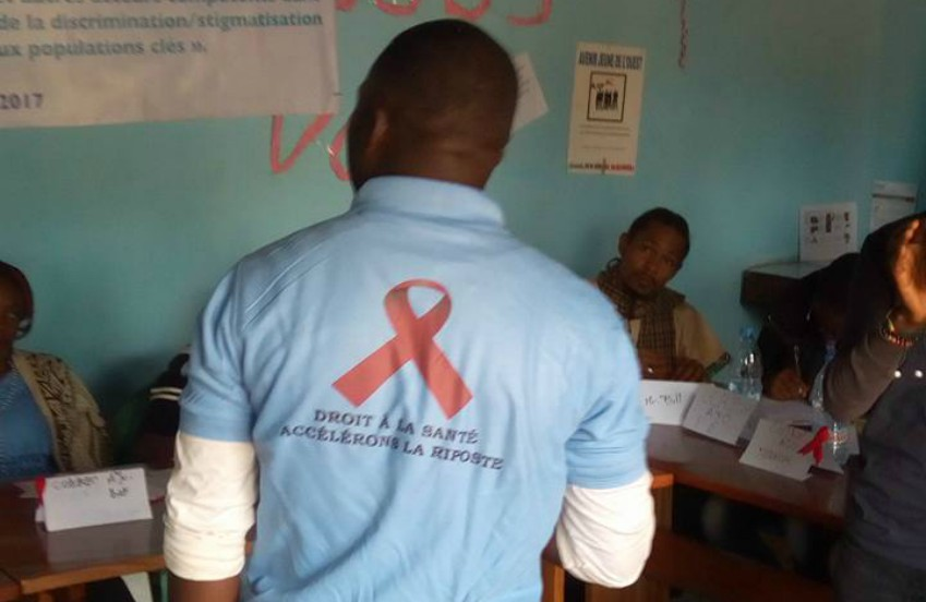 A photo of a man's back he's wearing a blue polo with the red aids ribbon on it, he is standing in a classroo