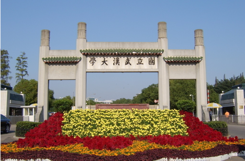 The big cement entrance to wuhan university is big with chinese writing along the top, a bed of colourful flowers sits underneath it