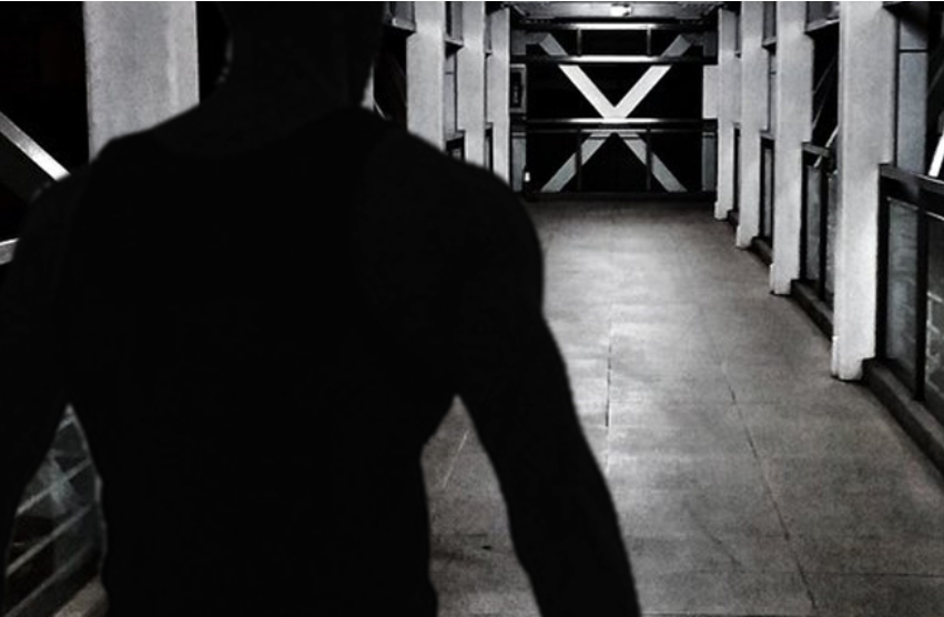 a grainy black and white photo with the back of a man facing the camera