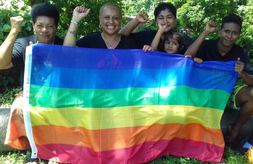A group of four women and one child sitting and holding a rainbow flag across them, they all have their right fists raised
