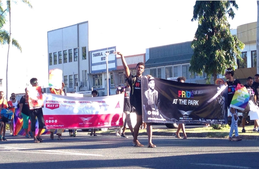 People walking down the street with banners and rainbow flags, one person is waving their hand in the air