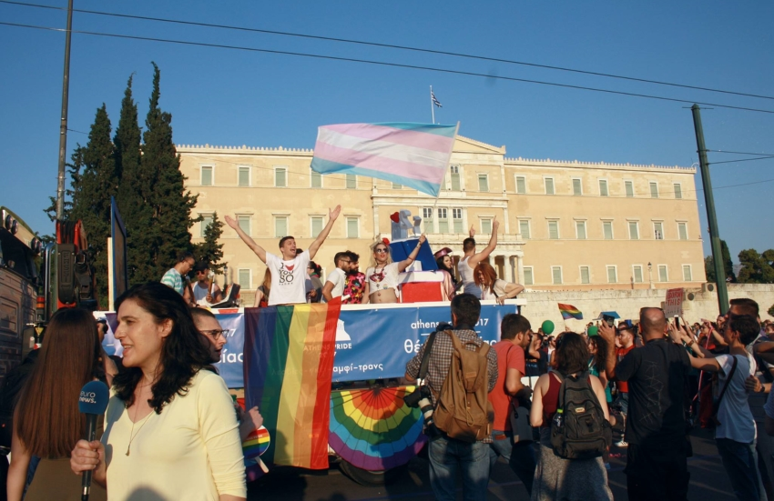 People standing on a bus with their arms in the air on a sunny day. One person is holding the transgender flag and a rainbow flag is draped on the side of the bus.