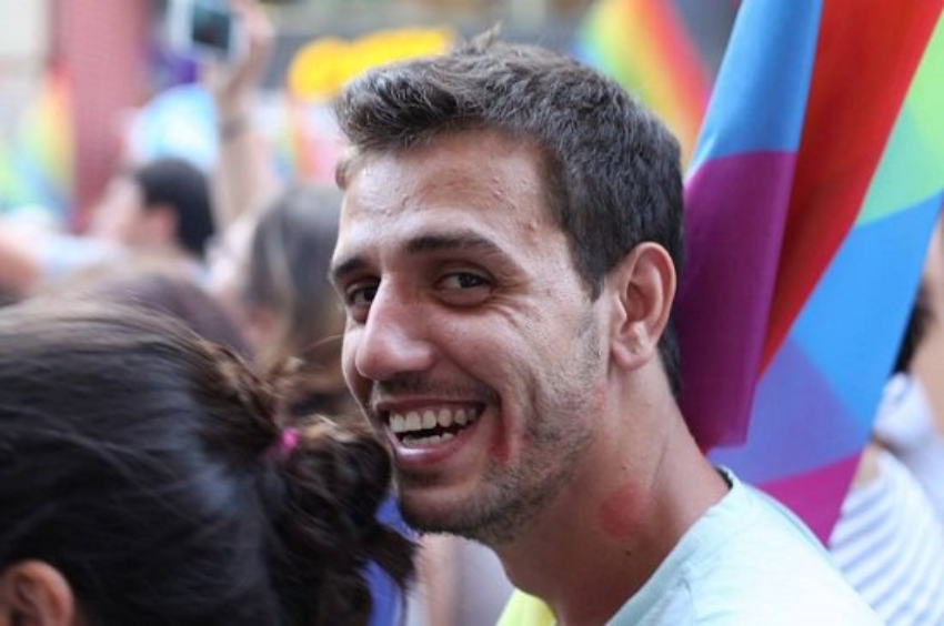 A candid shot of a man in a crowd who is looking over his shoulder and smiling at the camera. he is holding a rainbow flag