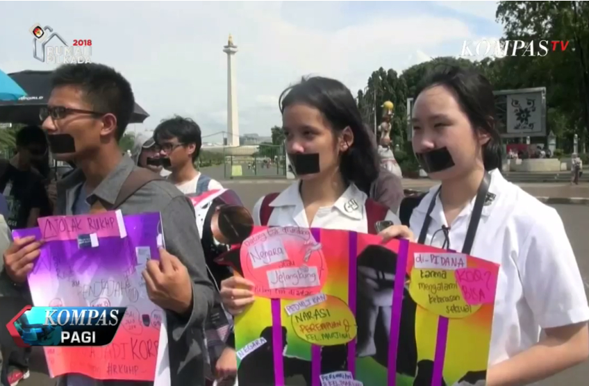 young students stand in a street holding handmade signs and with black masking tape over their mouths