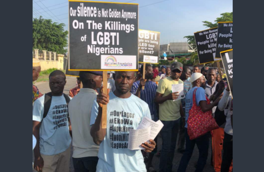 a man holding a placard at a protest saying 'our silence is not golden on the killings of lgbti nigerians'