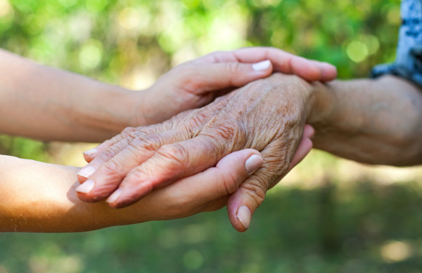 A young person holds the hand of an older person - carers are being asked to do better