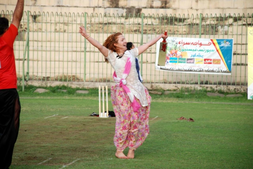 A transwoman is celebrating with her hands in the air holding a cricket bat