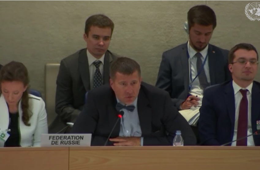 A man in a suit and bowtie leans into a microphone at a desk, there's three other people around him in suits listening to what he's saying. There's a paper plaque in front of him saying Russian Federation in French