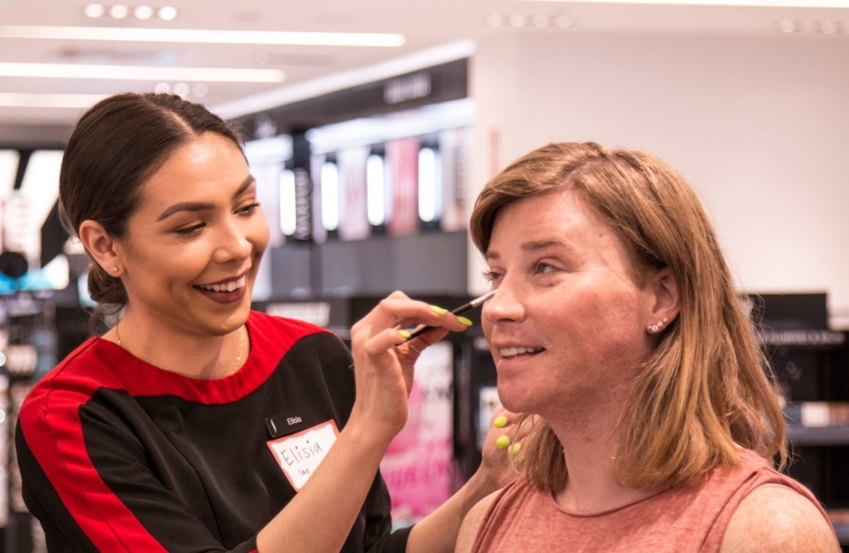 a beauty consultant is applying makeup to a person sitting down they are both smiling