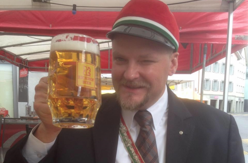 A man holds up a mug of beer and is wiking at the camera. He has some traditional swiss outfits on including a hat