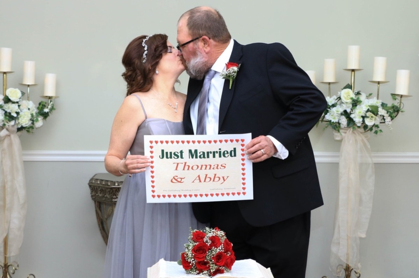 A couple stand facing each other in a chapel they are kissing and holding a sign saying 'just married thomas and abby'