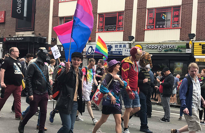 A marcher carries the flag for bi visibility at Birmingham Pride in England.