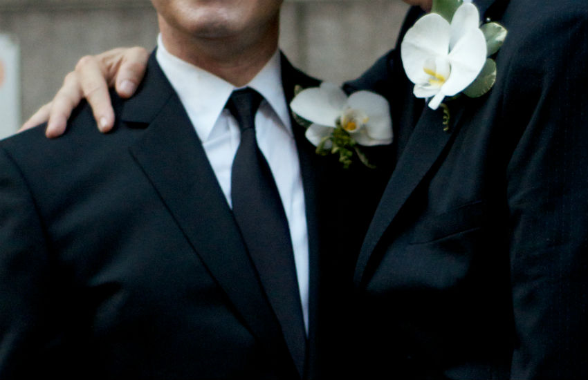 Two men in suits getting a civil partnership