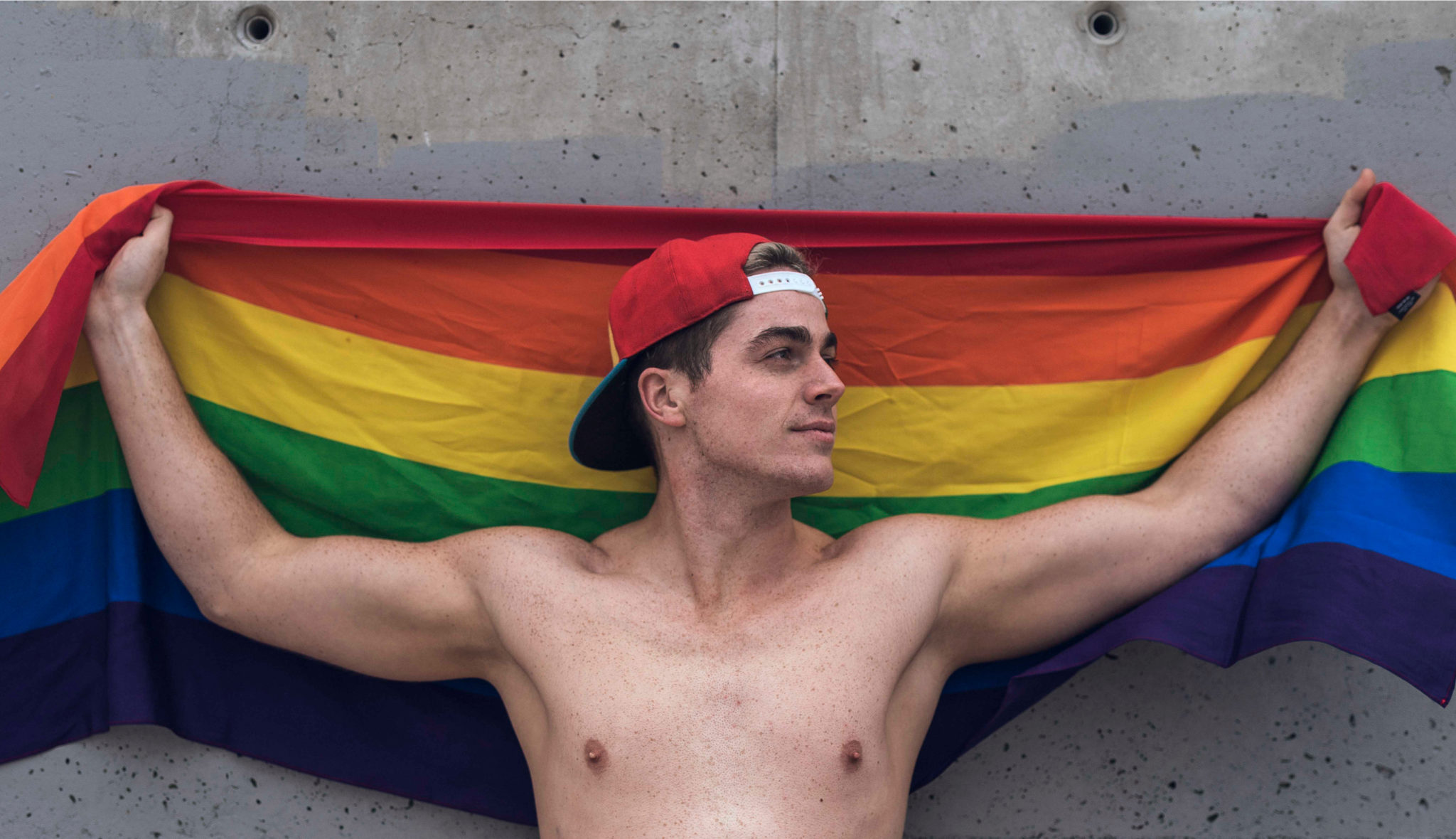 a topless man wearing a backwards cap is standing against a wall with the pride scarf strectched over his shoulders behind him