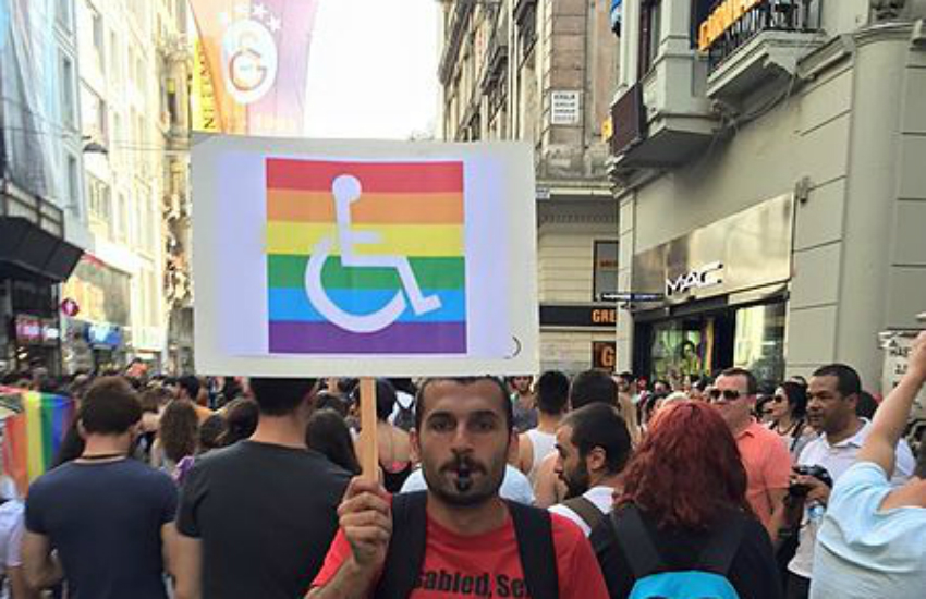 A man holds up a sign supporting LGBTI people in wheelchairs, Istanbul Pride 2015.